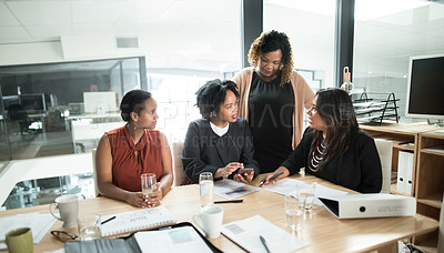 Buy stock photo Shot of a group of young businesswomen using a smartphone together during a boardroom meeting