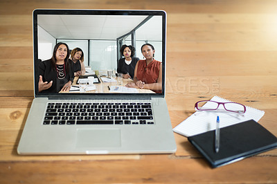 Buy stock photo Shot of a group of young businesswomen having a video conference on a laptop