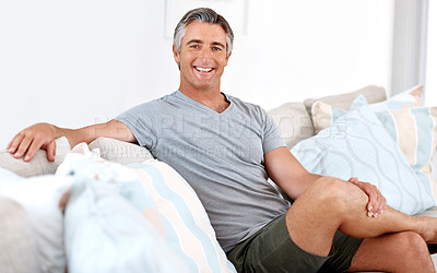 Buy stock photo Cropped portrait of a handsome mature man sitting on his living room sofa alone during the day