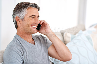 Buy stock photo Cropped shot of a handsome mature man sitting on his living room sofa alone and talking on his cellphone