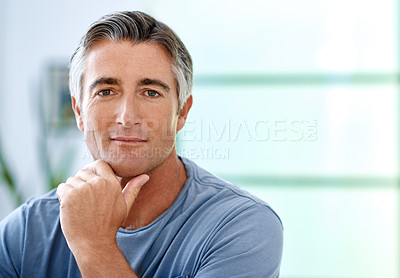 Buy stock photo Cropped portrait of a handsome mature man sitting with his hand on his chin while indoors in his house