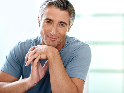 Buy stock photo Cropped portrait of a handsome mature man sitting and posing while inside his house during the day