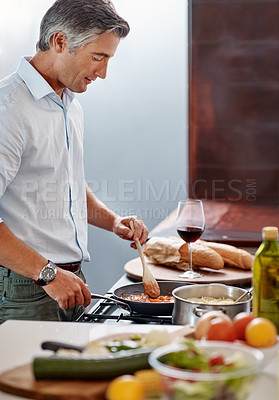 Buy stock photo Cropped shot of a handsome mature man cooking dinner in his kitchen at home