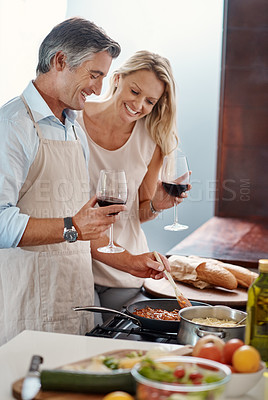 Buy stock photo Cropped shot of an affectionate mature couple drinking wine while cooking dinner in their kitchen at home