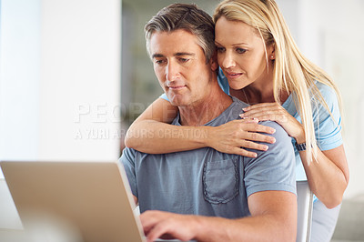 Buy stock photo Cropped shot of an attractive mature woman hugging her handsome mature husband while he uses a laptop in the house