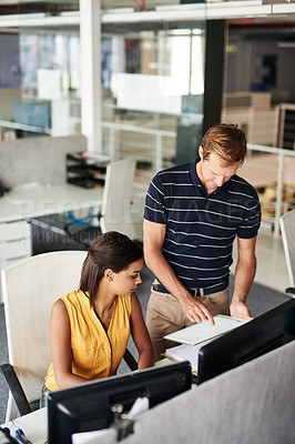 Buy stock photo Cropped shot of two business colleagues working on paperwork in their office
