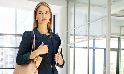Buy stock photo Cropped portrait of an attractive young businesswoman standing alone in a modern office and holding a tablet