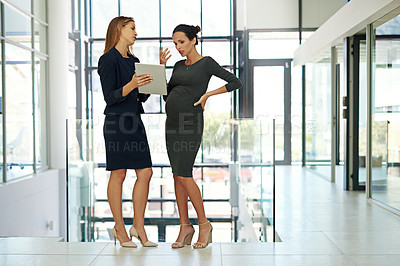 Buy stock photo Full length shot of two attractive young businesswomen standing together in a modern office and working on a tablet