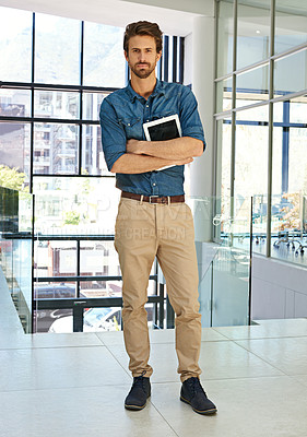 Buy stock photo Full length portrait of a handsome young businessman standing alone in a modern office and holding a tablet