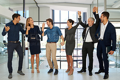 Buy stock photo Full length shot of a diverse group of businesspeople holding hands and celebrating together while standing in a modern office