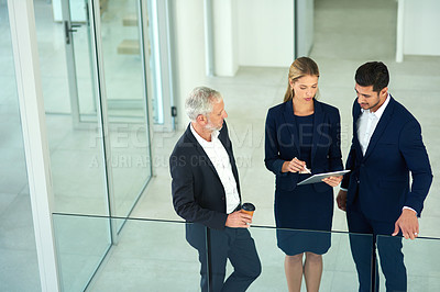 Buy stock photo Cropped shot of a group of young businesspeople standing together in a modern office and using a tablet