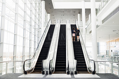 Buy stock photo Full length shot of two attractive businesswomen having a discussion while coming down an escalator in the workplace