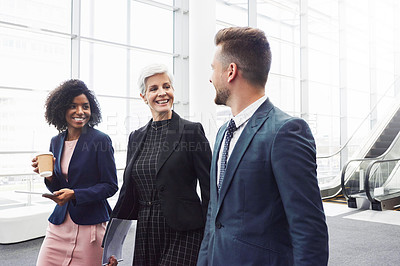 Buy stock photo Cropped shot of a diverse group of businesspeople having a discussion while walking through a modern workplace