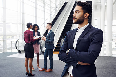 Buy stock photo Cropped shot of a handsome young businessman looking away thoughtfully in an office with his colleagues standing in the background