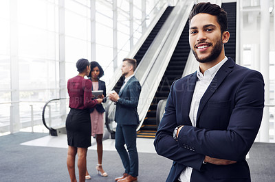 Buy stock photo Cropped portrait of a handsome young businessman standing in a modern workplace with his colleagues in the background