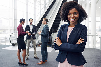 Buy stock photo Cropped portrait of an attractive young businesswoman standing in a modern workplace with her colleagues in the background
