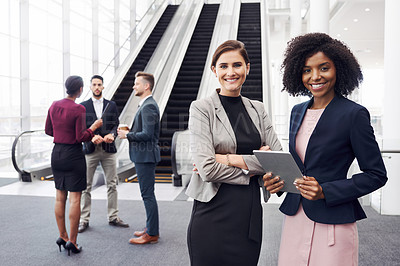 Buy stock photo Cropped portrait of two attractive young businesswomen using a digital tablet in an office with their colleagues in the background