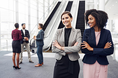 Buy stock photo Cropped shot of two attractive young businesswomen standing in an office with their colleagues in the background