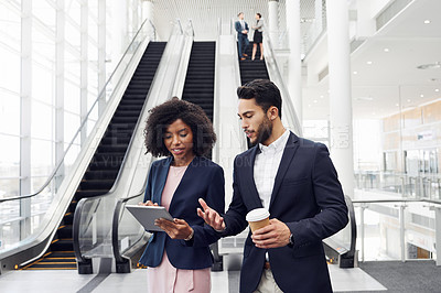 Buy stock photo Cropped shot of two young businesspeople using a digital tablet while having a discussion in a modern workplace