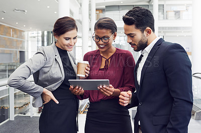 Buy stock photo Cropped shot of a diverse group of young businesspeople using a digital tablet while having a discussion in a modern workplace