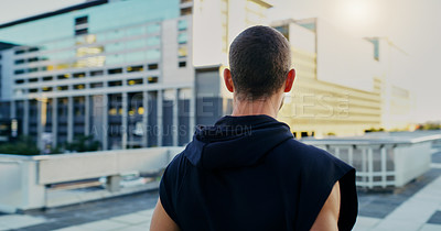 Buy stock photo Rearview shot of a young man going for a workout in the city