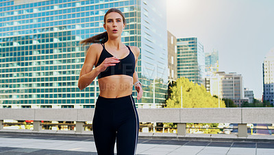 Buy stock photo Shot of a young woman going for a run in the city