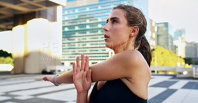 Buy stock photo Shot of a young woman stretching during her workout in the city