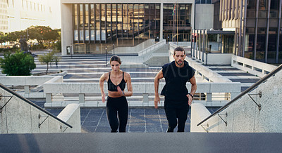 Buy stock photo Shot of a young man and woman running up stairs together in the city