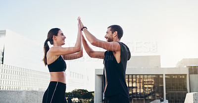 Buy stock photo Shot of a young couple giving each other a high five during their workout in the city