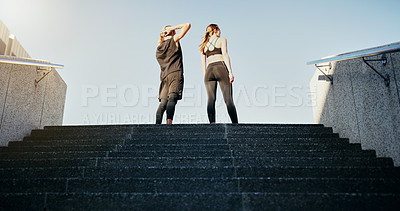 Buy stock photo Rearview shot of a young man and woman running up stairs together in the city