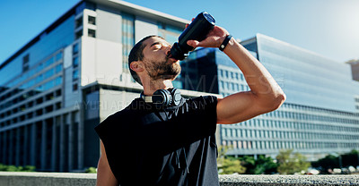 Buy stock photo Shot of a young man drinking water during his workout in the city