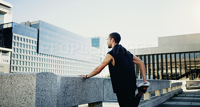 Buy stock photo Shot of a young man stretching during his workout in the city