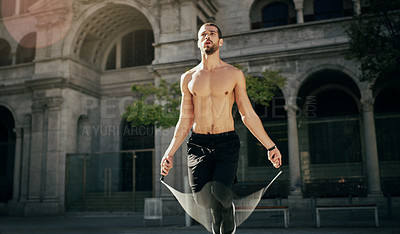 Buy stock photo Shot of a young man working out with a jump rope in the city