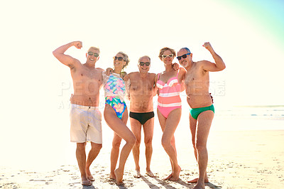 Buy stock photo Full length shot of a group of senior friends standing together while enjoying a day at the beach