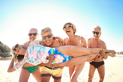 Buy stock photo Cropped shot of a group of senior friends carrying their female friend while enjoying a day at the beach