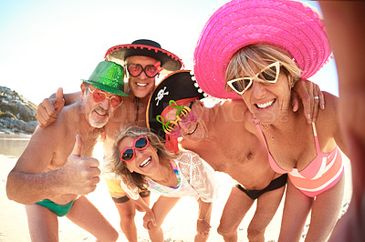Buy stock photo Cropped portrait of a group of senior friends taking a selfie together while enjoying a day at the beach