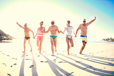 Buy stock photo Full length shot of a group of senior friends running together on the beach during the day
