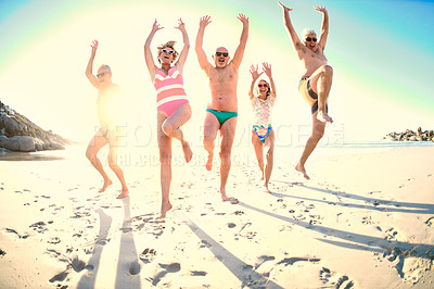 Buy stock photo Full length shot of a group of senior friends jumping into the air while enjoying a day at the beach