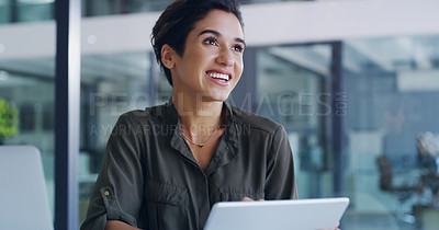 Buy stock photo Shot of an attractive young businesswoman feeling cheerful while using a digital tablet in her office