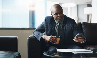 Buy stock photo Shot of a businessman using his cellphone while sitting in a modern office