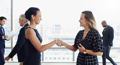 Buy stock photo Cropped shot of two businesspeople shaking hands while colleagues are blurred in the background