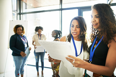 Buy stock photo Cropped shot of two young businesswomen discussing a document during a conference