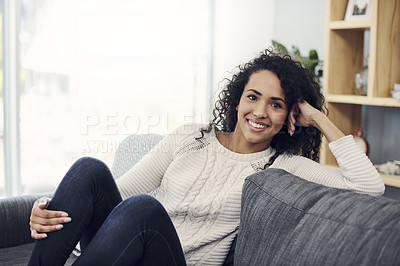 Buy stock photo Cropped portrait of an attractive young woman smiling while relaxing on her couch at home