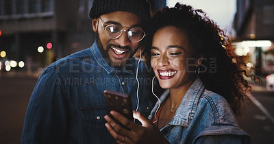 Buy stock photo Shot of a young couple using a smartphone and earphones in the city