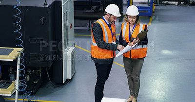 Buy stock photo Shot of two engineers discussing paperwork in an industrial place of work
