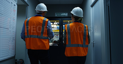 Buy stock photo Rearview shot of two engineers walking through an industrial place of work