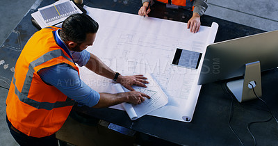 Buy stock photo High angle shot of two engineers going over a blueprint together in an industrial place of work