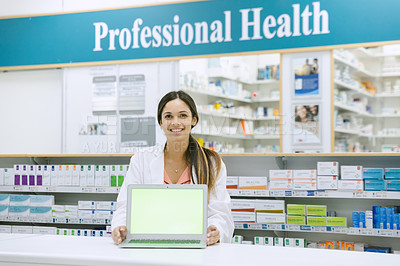 Buy stock photo Shot of a pharmacist holding a laptop displaying chroma key on the screen