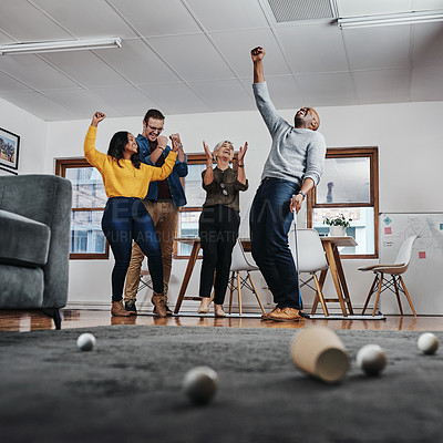 Buy stock photo Full length shot of a businessman playing golf in his office with his colleagues rooting for him in the background