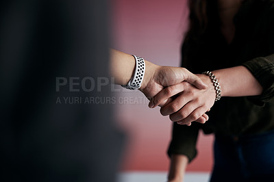 Buy stock photo Cropped shot of two unrecognizable coworkers shaking hands in agreement while standing in the office